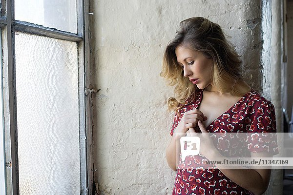 Beautiful young woman in red dress by the window hands over heart.