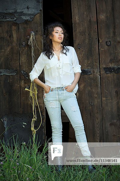 Beautiful young woman in faded  distressed jeans and white top  standing full length at the door of an old barn.