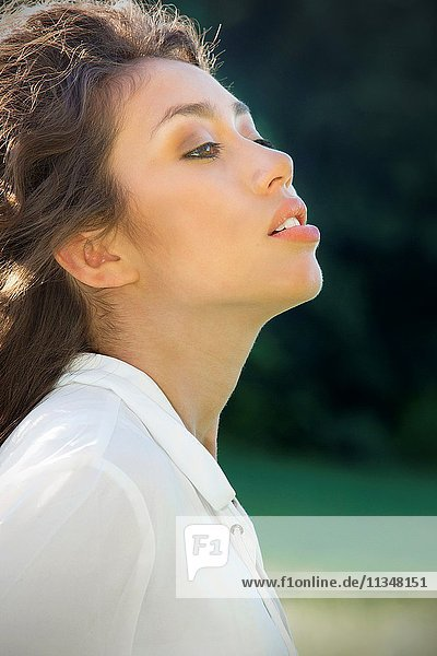 Outdoor portrait of beautiful young Latina woman in white blouse on a sunny day with woods in the background.