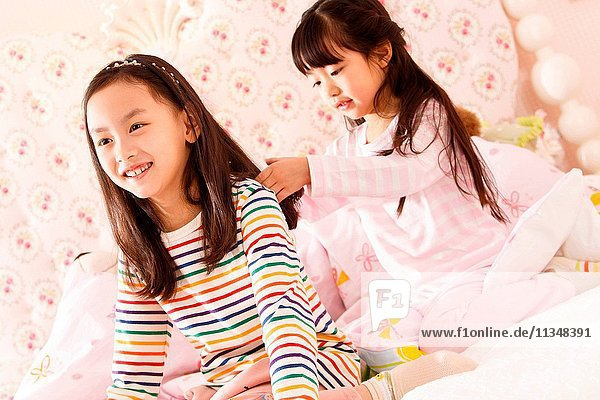 Two little girls are playing on the bed