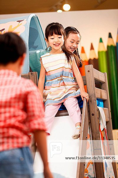 Happy children play on the bed
