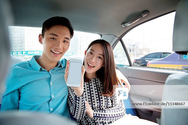 Young lovers in the car holding a mobile phone navigation