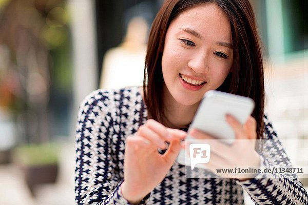 Young girl watching mobile phone