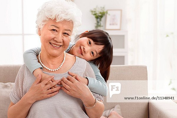 Cute little girl and grandmother in the living room