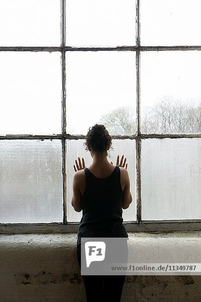 Rear view of a young woman standing by the window hands touching the glass.