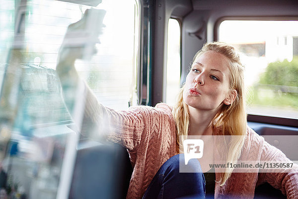 Junge Frau im Auto macht ein Selfie