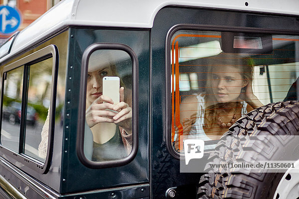 Zwei junge Frauen mit Handy in einem Geländewagen