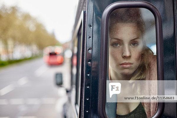 Ernste junge Frau hinter einem Autofenster schaut hinaus