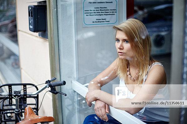Junge Frau hinter einer Fensterscheibe schaut hinaus