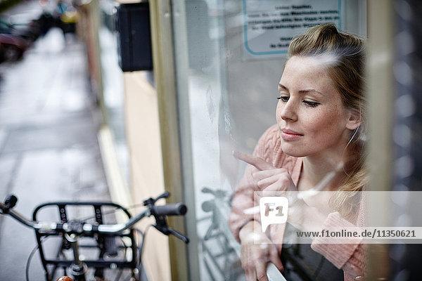 Junge Frau hinter einem Fenster zeichnet an die Scheibe