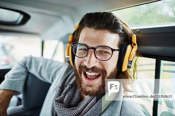 Fröhlicher Mann mit Vollbart im Auto trägt Kopfhörer
