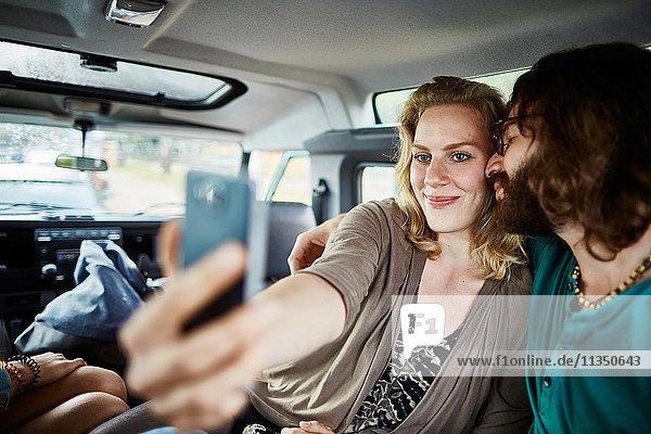 Happy couple taking a selfie in car