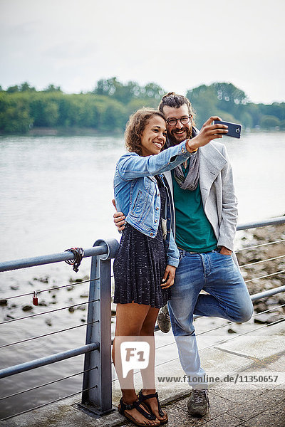 Junges Paar macht ein Selfie am Flussufer