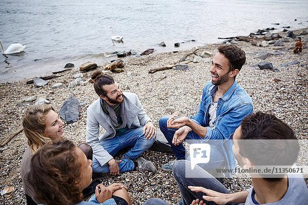 Fröhliche Freunde sitzen zusammen am Flussufer