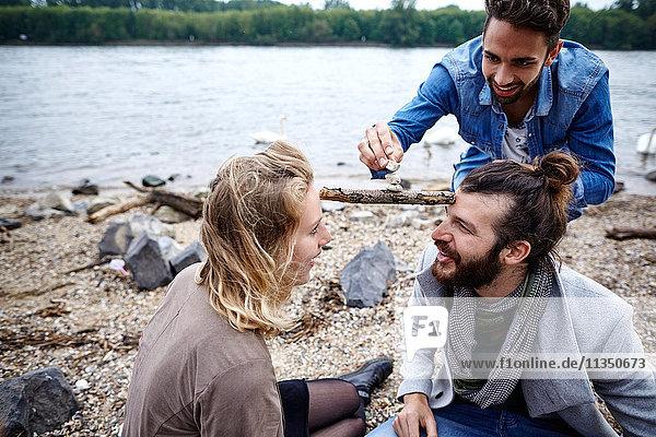 Freunde am Flussufer balancieren Stock und Steine