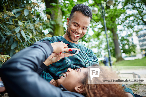 Glückliches junges Paar mit Handy auf einer Parkbank