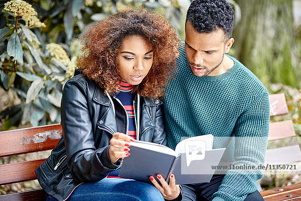 Young couple on park bench reading a book together