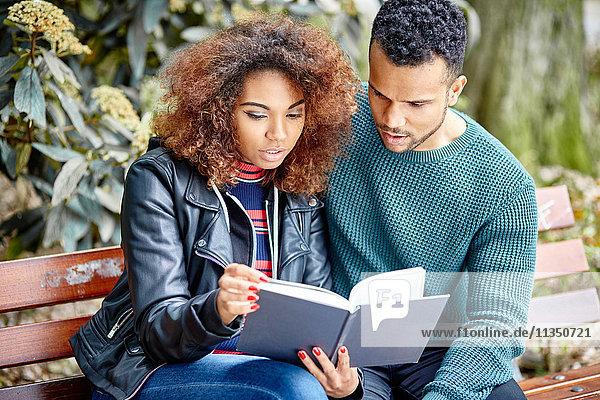 Junges Paar auf einer Parkbank liest zusammen ein Buch