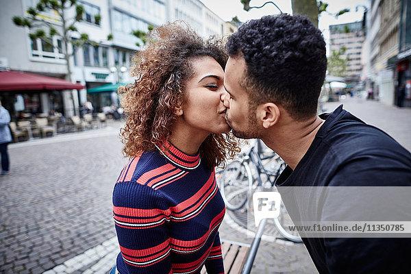 Junges Paar küsst sich in der Stadt