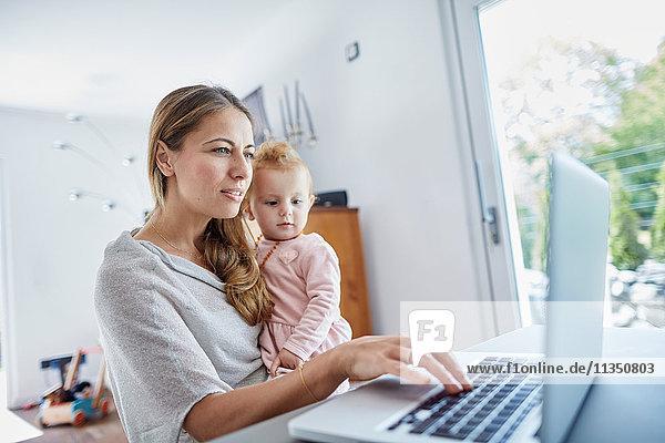 Mutter mit Baby benutzt einen Laptop Zuhause