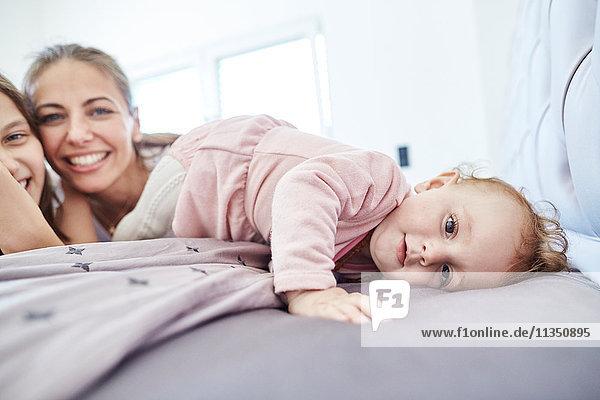 Baby mit Mutter und Schwester im Bett