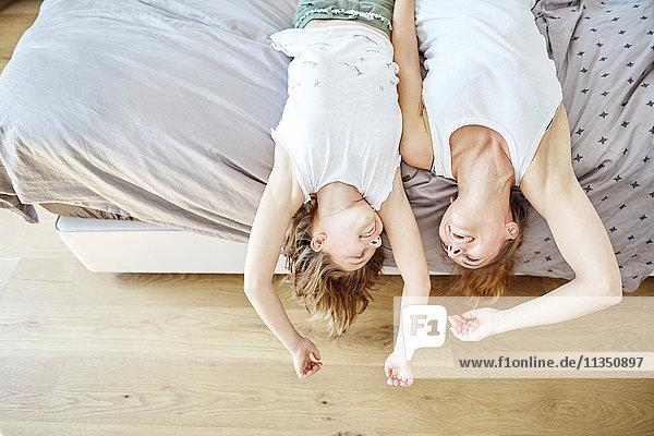Fröhliche Mutter und Tochter liegen im Bett