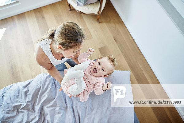 Mutter wirft Baby hoch in die Luft