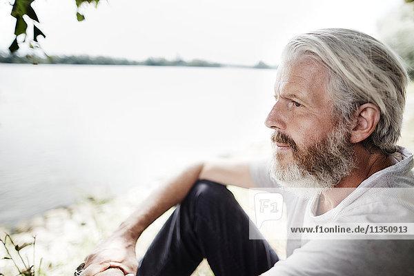 Reifer Mann mit Vollbart am Flussufer