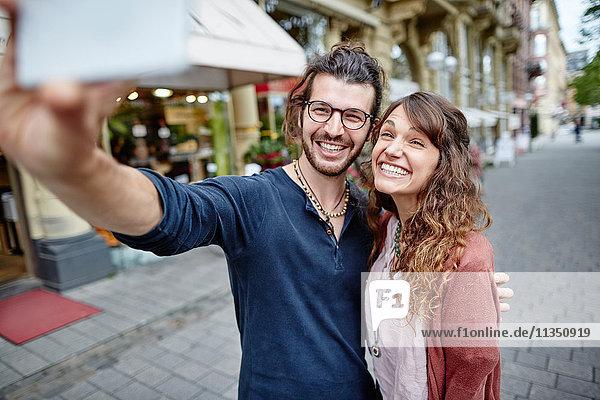 Lächelndes junges Paar macht ein Selfie in der Stadt
