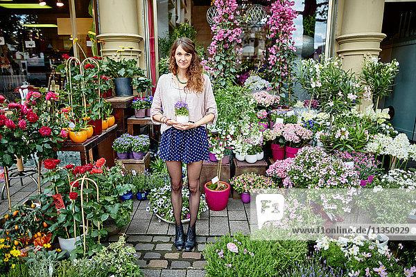 Junge Frau steht an einem Blumengeschäft