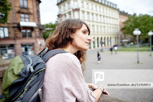 Junge Frau mit Rucksack in der Stadt