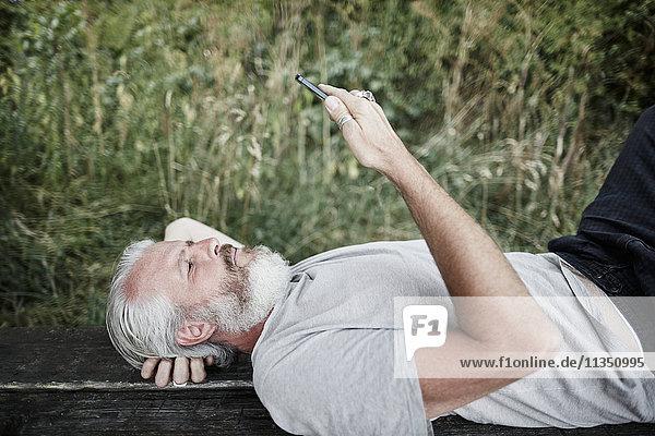 Reifer Mann mit Vollbart liegt auf einer Bank und schaut auf Handy