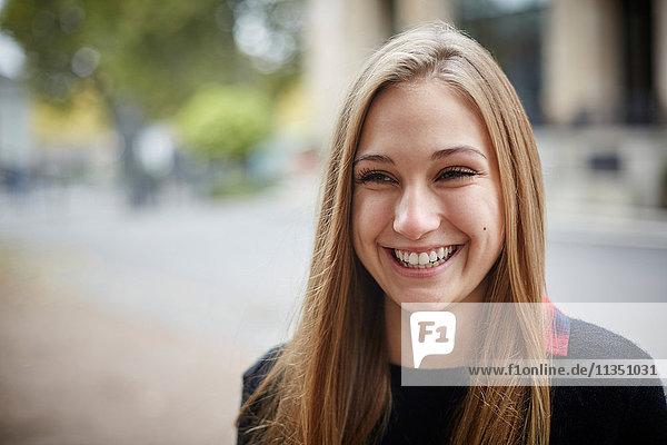 Portrait einer lächelnden jungen Frau im Freien