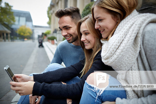 Drei lächelnde Freunde schauen zusammen auf ein Handy