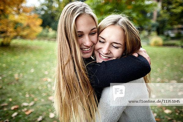 Zwei glückliche junge Frauen umarmen sich im Freien