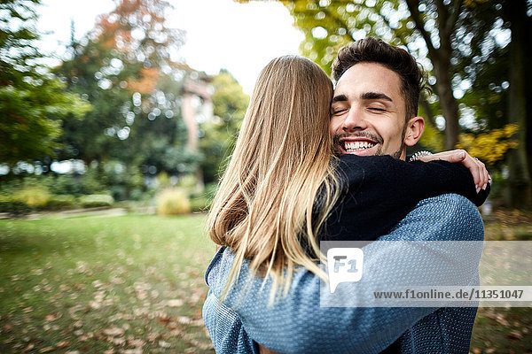 Happy young couple hugging in park