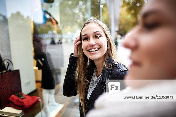 Zwei junge Frauen schauen in ein Schaufenster