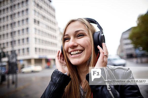 Fröhliche junge Frau mit Kopfhörern im Freien
