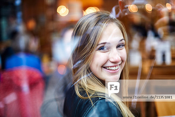 Portrait of smiling young woman reflected in window