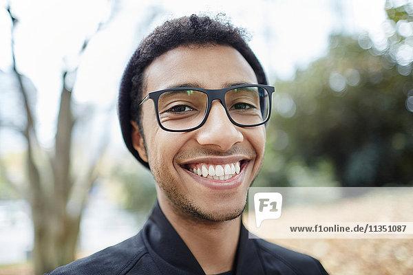 Portrait eines lächelnden jungen Mannes mit Brille im Freien
