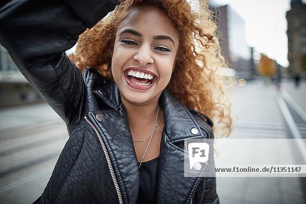 Portrait einer lachenden Teenagerin in Lederjacke