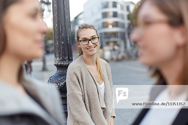 Lächelnde Frau in der Stadt mit zwei Frauen im Vordergrund