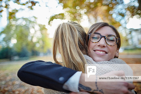 Zwei lächelnde Frauen umarmen sich im Park
