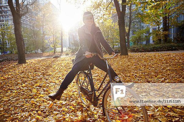 Fröhliche Frau auf Fahrrad in herbstlichem Stadtpark