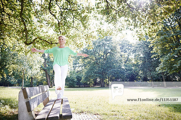Reife Frau balanciert auf einer Parkbank