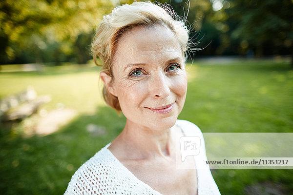 Portrait einer lächelnden reifen Frau im Park