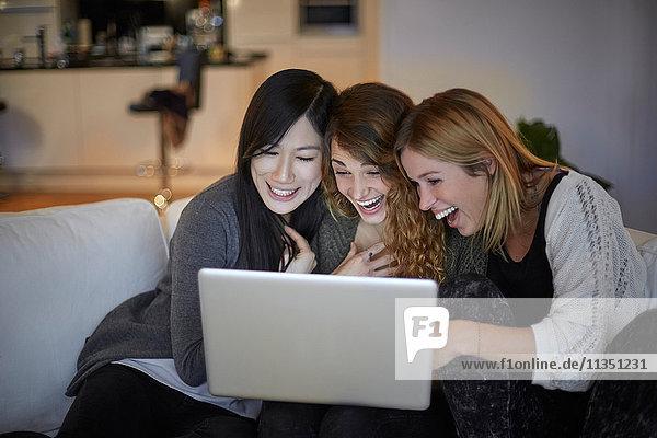 Drei fröhliche Frauen sitzen auf der Couch und schauen zusammen auf einen Laptop