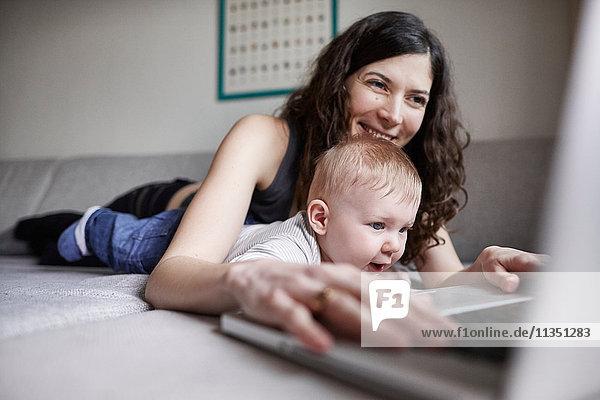 Frau mit Baby auf der Couch benutzt Laptop