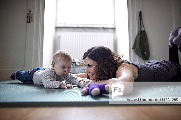 Mutter und Baby liegen auf einer Matte auf dem Fußboden