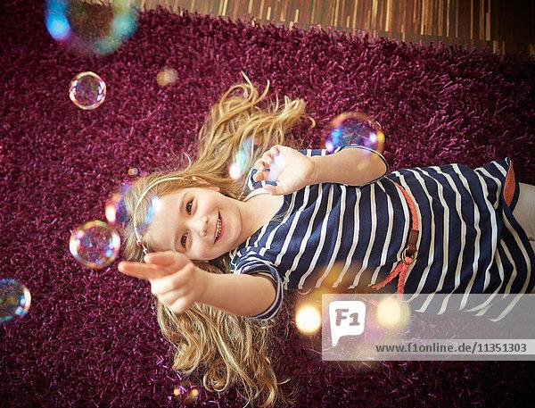 Glückliches Mädchen liegt auf einem Teppich und spielt mit Seifenblasen